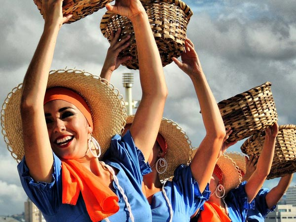 Costa Rica women wearing traditional clothing and raising baskets